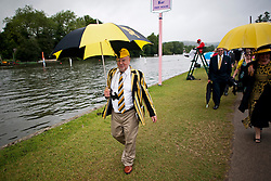 © London News Pictures. 03/07/2013.  Henley-on-Thames, UK.  A man in rowing colours shelters from the rain on Day one of Henley Royal Regatta on the River Thames at Henley-on-Thames, Oxfordshire on July 03, 2013. Photo credit: Ben Cawthra/LNP