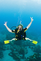 A female diver poses for the camera with peace signs, St. Lucia.