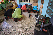 A general picture shows members of the Free Syrian Army (FSA) taking a moment to pray as they prepare for a military operation on Monday, June 25, 2012 - following a three days government ground and airstrikes. It bears the scars from Syrian President Bashar al-Assad's use of military force to crush an opposition movement that has spawned an armed insurgency against his rule. (Photo by Vudi Xhymshiti)