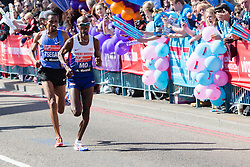 © Licensed to London News Pictures. 13/04/2014. London, UK. Mo Farah is cheered by the crowd as he crosses the half way point at Tower Bridge during the London Marathon today followed behind by Samuel Tsegay. Photo credit : Vickie Flores/LNP