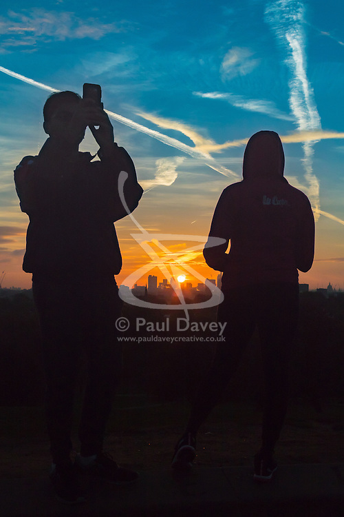 Primrose Hill, London, October 28th 2016. A couple take pictures and watch the sunrise over the city skyline as dawn breaks over London.