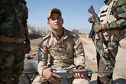 © Licensed to London News Pictures. 04/11/2016. Hamdaniyah, Iraq. Militiamen of the Nineveh Plain Protection Units (NPU), an Assyrian Christian militia that is working with the Iraqi Army to retake Christian areas, guard a checkpoint in the recently liberated Christian town of Hamdaniyah, Iraq.<br /> <br /> Although located close to a front line, littered with improvised explosive devices and pieces of unexploded ordnance the Christian town of Hamdaniyah has only recently been cleared of ISIS extremists who stayed behind to fight. After the town's liberation as part of the Mosul Offensive residents and priests of the town are now free to take short trips to assess damage, salvage possessions and clear up the mess left by militants during their two year occupation.<br /> <br /> Hamdaniyah, and much of the Nineveh plains, were captured by the Islamic State during a large offensive on the 7th of August 2014 that saw the extremists advance to within 20km of the Iraqi Kurdish capital Erbil. Residents of the town, who included many Christian refugees who escaped there after the fall of Mosul, were then forced to seek sanctuary in the Kurdish areas. In the year and two months of the ISIS occupation churches were burnt, homes were put into use as militant accommodation and bomb factories and some buildings destroyed by coalition airstrikes. Photo credit: Matt Cetti-Roberts/LNP