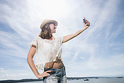 Woman taking selfie at the lake, Ammersee, Upper Bavaria, Germany