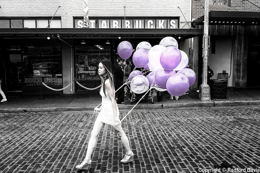 A young woman with bright balloons walks past the original Starbucks in Pike Place market, Seattle, Washington, B&W, black and white