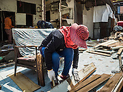 21 SEPTEMBER 2015 - BANGKOK, THAILAND: A demolition worker takes nails out of scrap lumber from homes being torn down near Wat Kalayanamit. Fiftyfour homes around Wat Kalayanamit, a historic Buddhist temple on the Chao Phraya River in the Thonburi section of Bangkok are being razed and the residents evicted to make way for new development at the temple. The abbot of the temple said he was evicting the residents, who have lived on the temple grounds for generations, because their homes are unsafe and because he wants to improve the temple grounds. The evictions are a part of a Bangkok trend, especially along the Chao Phraya River and BTS light rail lines. Low income people are being evicted from their long time homes to make way for urban renewal.    PHOTO BY JACK KURTZ