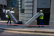 Workmen deliver staff security lockers to a new City of London business development. In a side street near insurance house Lloyds of London in the heart of capital's financial district (founded by the Romans in the 1st Century), the two workmen carefully push and pull the lockers towards the site nearby. With safety tape stretched across the pavement, the men observe other safety considerations in hi-viz tabards.