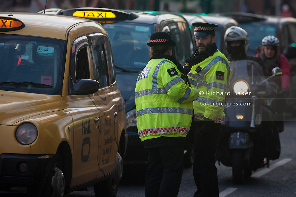City of London police officers not the license numbers of black London cabs while they protest about their being banned from City road junctions, on 18th January 2017, in Parliament Square, London England.