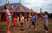 Schoolchildren of various ages learn circus skills from a circus performer with the small Snapdragon Circus, on 28th September 1990, in London, England.