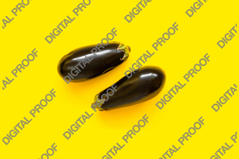 Pair of eggplants isolated in yellow background viewed from above - flatlay look