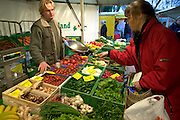 "At the outdoor Friday market in their tidy community of Bargteheide, Germany, Susanne Melander buys organic (""bio"") vegetables from a greengrocer. (Supporting image from the project Hungry Planet: What the World Eats.)"