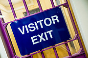 The visitor exit sign on a locked gate in the visiting hall of HM Prison Brixton, a local men's prison located in Brixton in the borough of Lambeth in South London on the 26th of July 2016, London United Kingdom. The prison originally opened  as the Surrey House of Correction in 1820 and now has a capacity of 800 men living across 5 different wings. (photo by Andy Aitchison)