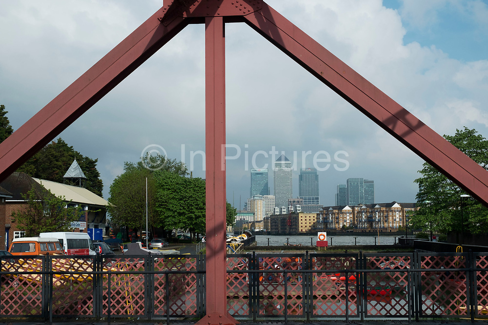 View of the Docklands area, Canary Wharf and financial district through a Brunel bridge in Wapping, London, England, United Kingdom.