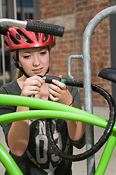 Teenage girl locking bicycle