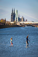 man and woman on slacklines in the Rhine harbor in the district Deutz, in the background the cathedral and Severins bridge, Cologne, Germany.<br /> <br /> Mann  und Frau auf Slacklines im Deutzer Hafen am Rhein, im Hintergrund der Dom und Severinsbruecke, Koeln, Deutschland.