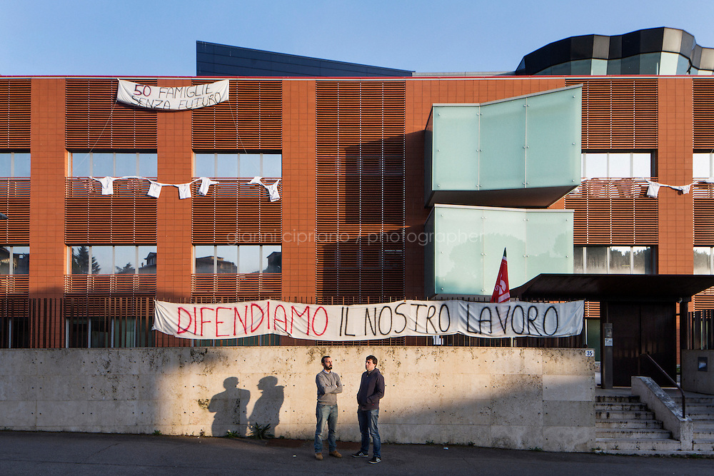 """SIENA, ITALY - 20 MARCH 2015: (L-R) Facility manager Michele Midollini (35) and researcher Massimiliano Travagli (40), two lab representatives of Siena Biotech, pose for a portrait in front of the headquarters they occupied together with other 48 employees to protest against the financial cutback of the Monte dei Paschi di Siena Foundation, in Siena, Italy, on March 20th 2015. The banners set up on the gate and on the building say """"We defend our work"""" and """"50 families without a future"""".<br /> <br />  Siena Biotech is a clinical-stage drug discovery company whose  efforts are mainly focused on discovering new drugs for therapeutic intervention against neurodegenerative diseases and in oncology, such as Alzheimer's Disease, Huntington's Disease and Cancer. Until 2014 Siena Biotech was entirely funded by the Monte dei Paschi di Siena Foundation.<br /> <br /> Now Siena Biotech has filed for bankruptcy proceedings, and its researchers and employees occupied the headquarters of the company based in Siena.<br /> <br /> Siena, a Tuscan city and UNESCO World Heritage Site, is home to Monte dei Paschi di Siena, the world's oldest surviving bank and Italy's third largest bank. The bank, founded in 1472, was the largest employer in Siena, and it helped finance a host of community projects and services until it stumbled during the financial crisis started in 2008."""