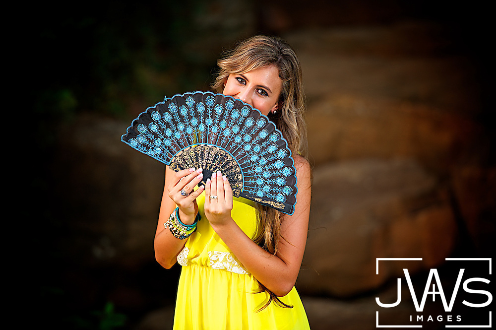 Young lady in a yellow dress holding a blue fan across her face for her senior picture.