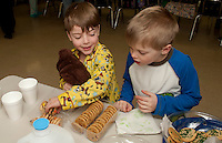 Andrew Hosmer and Tommy Demeroto enjoy some milk and cookies after listening to stories told by parent volunteers Tuesday evening during Holy Trinity Catholic School's book fair and reading time.  (Karen Bobotas/for the Laconia Daily Sun)