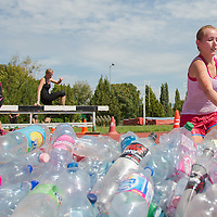 Competitors run through plastic bottles during the Brutal Run extreme obstacle course race in Budapest, Hungary on August 30, 2014. ATTILA VOLGYI
