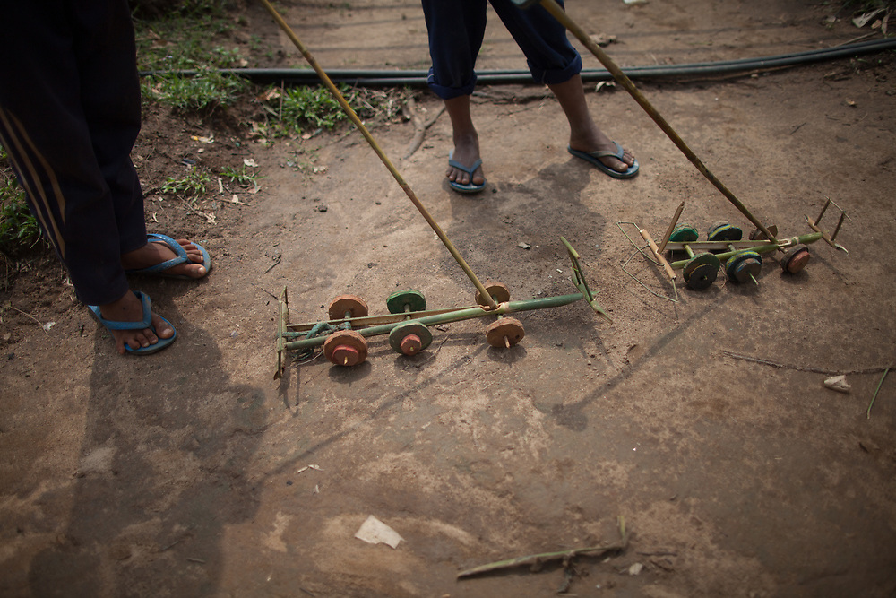 Two boys play with toy lorries they've made themselves from bamboo and broken flipflops.