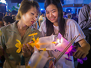 04 MARCH 2015 - BANGKOK, THAILAND: Women light candles before the procession around the prayer hall at Wat Benchamabophit on Makha Bucha Day. Makha Bucha Day is an important Buddhist holy day and public holiday in Thailand, Cambodia, Laos, and Myanmar. Many people go to temples to perform merit-making activities on Makha Bucha Day. Wat Benchamabophit is one of the most popular Buddhist temples in Bangkok.    PHOTO BY JACK KURTZ
