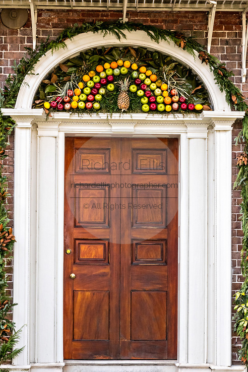 Traditional tropical fruit fan Christmas decorations above the doorway to the historic Nathaniel Russell House and museum on Meeting Street in Charleston, South Carolina. A fruit fan of was a traditional sign of hospitality during Colonial times and still honored in Charleston.