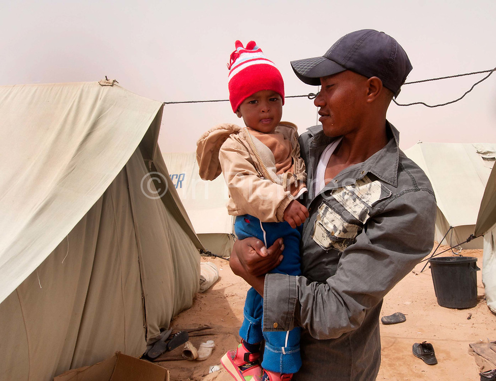 Merlin in Tunisia. Shousha camp for migrant workers displaced from Libya February to May 2011. Father and child