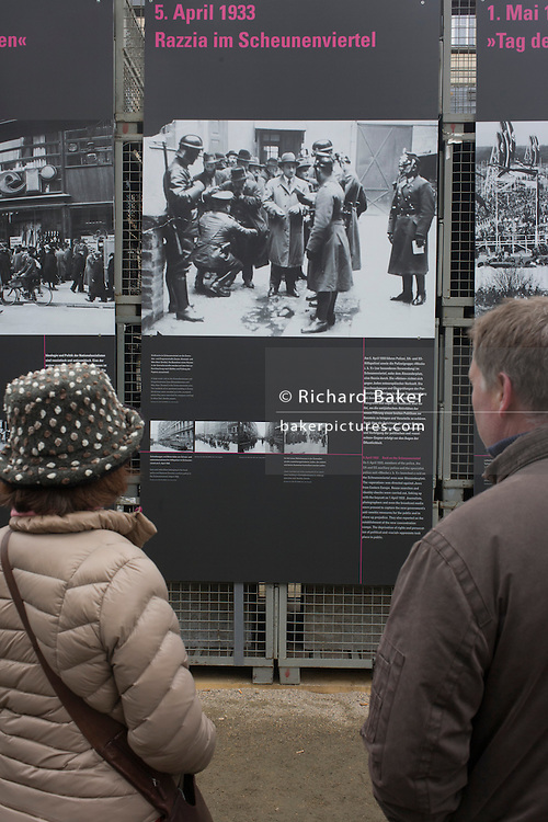 Tourists learn more about German history by reading outdoor exhibition panels telling the story of Nazi fascism during the 1930s and 40s, in Unter den Linden and opposite the Brandengurg Gate.