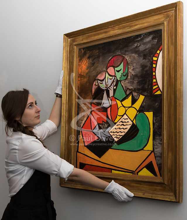 """Sotheby's, London, June 19th 2015. International auctioneers Sotheby's gears up to holding what they say is London's highest valued auction of contemporary artworks, to be held on June 24th 2015 where the combined artworks are anticipated to bring in as much as £203 million. PICTURED: A Sotheby's gallert technician hangs Pable Picasso's """"Deux Personnages """", an oil on canvas that was inspired by the artist's beloved mistress Marie-Therese Walter and  is anticipated to fetch between £13-18 million at auction.  // Payment/Licencing/Contact details: Paul@pauldaveycreative.co.uk Tel: 07966016296"""