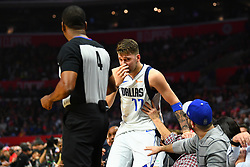 December 21, 2018 - Los Angeles, CA, U.S. - LOS ANGELES, CA - DECEMBER 20: Dallas Mavericks Guard Luka Doncic (77) grabs his nose after falling into the stands and being knocked in the face by the official during a NBA game between the Dallas Mavericks and the Los Angeles Clippers on December 20, 2018 at STAPLES Center in Los Angeles, CA. (Photo by Brian Rothmuller/Icon Sportswire) (Credit Image: © Brian Rothmuller/Icon SMI via ZUMA Press)