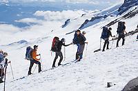Rainier Mountaineering Guides meet their climbing clients as they arrive at camp Muir 10000 feet up Mt Rainier, Washington, Unitede States.