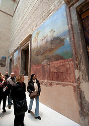 Visitors looking at old mural on wall in Egyptian courtyard gallery of newly renovated Neues Museum on the Museuminsel in central Berlin reopened after many years construction work Architect David Chipperfield March 2009