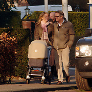 NLD/Laren/20060114 - Presentator Fons de Poel wandeld in ondergaande zon met partner Saskia en dochter Mazarine in de kinderwagen door Laren, achter hen zijn schoonouders