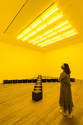 """© Licensed to London News Pictures. 05/10/2020. LONDON, UK.  London, UK.  5 October 2020. A staff member views """"Black Marble Under Yellow Light"""" 1981/1988.  Preview of Bruce Nauman at Tate Modern, the first new exhibition since the reopening of the gallery after coronavirus lockdown restrictions were eased.  This exhibition is the first to show Nauman's full breadth of work in London for more than 20 years, with sculpture, sound, film, video and neon works during his 50-year career on display 7 October 2020 – 21 February 2021.  Photo credit: Stephen Chung/LNP"""