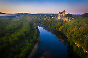 """The Château de Montfort is a castle in the French commune of Vitrac in the Dordogne département, part of the region of Nouvelle-Aquitaine.<br /> <br /> The castle clings to a promontory overlooking the Cingle de Montfort (Montfort Meander) on the Dordogne River. Its grandiose setting """"aroused the envy of those who wished to rule Périgord"""" so that its history is a long series of battles and sieges. It was taken and razed to the ground by Simon de Montfort in 1214. The castle was later rebuilt, but again destroyed another three times: during the Hundred Years' War, under Louis XI of France and on the instructions of Henri IV of France.<br /> <br /> Renovation work was carried out in the 19th century and gives the castle a """"whimsical look of a stage setting for light opera."""
