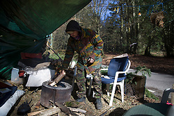 © Licensed to London News Pictures. 02/03/2017. Coldharbour, UK. A protestor makes a fire at the 'Protection Camp' on Leith Hill. Activists have constructed and occupied a fort and some trees on the site of a proposed oil well. Planning permission for 18 weeks of exploratory drilling was granted to Europa Oil and Gas in August 2015 after a four-year planning battle. The camp was set up by protestors in October 2016 in order to draw  attention to plans to drill in this Area of Outstanding Natural Beauty (AONB) in the Surrey Hills. The camp has received support from the local community.  Photo credit: Peter Macdiarmid/LNP