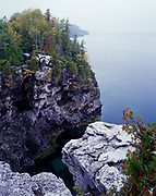Dolomite cliffs of the Niagara Escarpment rising above Georgian Bay, Lake Huron at the Grotto, Bruce Trail, Bruce Peninsula National Park, Ontario, Canada.