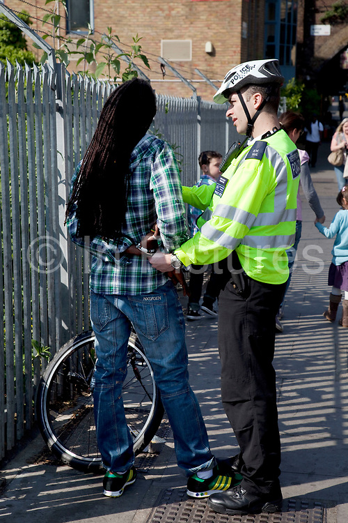 Black male being stopped by a police officer in Camden, London.The officer was talking to the unidentified man while restraining him with hand cuffs.