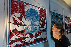 © Licensed to London News Pictures. 09/10/2020. LONDON, UK. A staff member views a series of silk hangings by Berke Yazicioglu, illustrating Stravinsky's The Rite of Spring, at the launch of The House of Bandits in Mayfair – a new art and fashion space by Sarabande Foundation.  The Foundation, established by the late Lee Alexander McQueen, supports and promotes creative talent.  Works by a selection of the 100 artists and designers that the Foundation has supported to date are presented in this new temporary store and gallery on Vigo Street, adjoining the Burberry Regent Street store.  The opening coincides with Frieze Week, and runs up to Christmas.  Photo credit: Stephen Chung/LNP