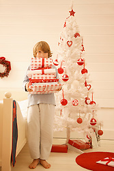 Boy standing by a Christmas tree holding a pile of gifts
