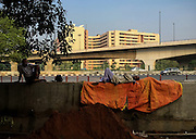 13th August 2015, New Delhi. A man sleeps on top of a wall in New Delhi, India on the 13th August 2015<br /> <br /> Sleeping in the outdoors is common in Asia due to a warmer climate and the fact that personal privacy for sleep is not so culturally ingrained as it is in the West. New Delhi (where most of these images were taken) is a harsh city both in climate and environment and for those working long hours, often in hard manual labour, sleep and rest is something fallen into when exhaustion overwhelms, no matter the place or circumstance. Then there are the homeless, in Delhi figures for them from Government and NGO sources vary wildly from 25,000 to more than 10 times that. Others public sleepers may simply be travellers having a siesta along the way.<br />  <br /> <br /> PHOTOGRAPH BY AND COPYRIGHT OF SIMON DE TREY-WHITE, photographer in Delhi<br /> <br /> + 91 98103 99809<br /> email: simon@simondetreywhite.com
