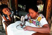 MEXICO, YUCATAN Mayan family near Chichen Itza; mother applying traditional colorful embroidery and being watched by her daughter