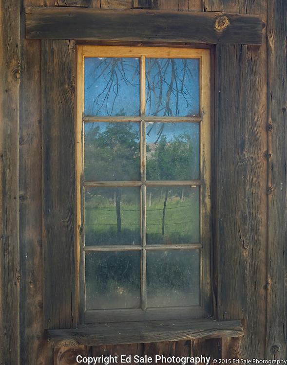 Window and reflection of trees in old wooden house in Grafton, Utah ghost town.  Location of bicycle scene from movie Butch Cassidy and the Sundance Kide