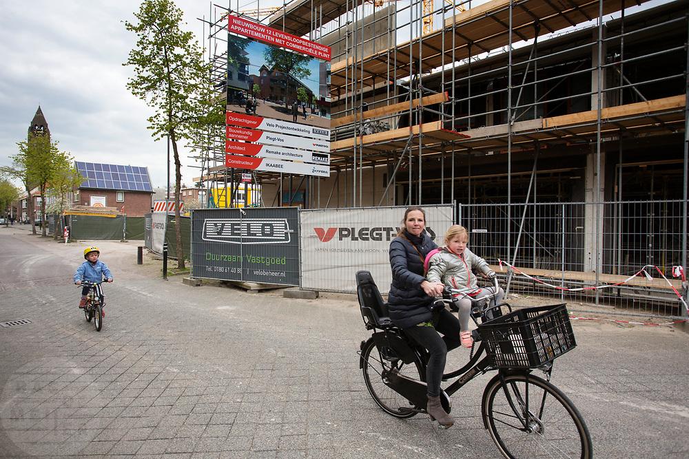 In Zeist fietst een moeder met haar kinderen langs een nieuwbouwproject in het centrum.<br /> <br /> In Zeist a woman cycles with her children at the city center.