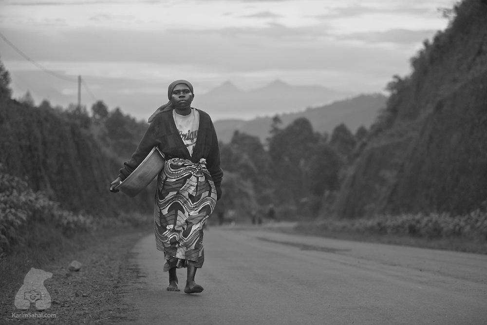 A woman walks on a road leading to Lake Kivu, near Kibuye, Rwanda. The distant hills are located in the Democratic Republic of Congo.