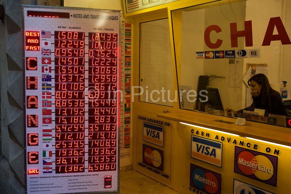 A bureau de change shop offers deals and best prices to tourists and Italian passers-by on a Florence street. With the countries' flags on the far left and across, are the buy and sell rates for the Euro. Lit with dot matrix numbers, the list of decimal figures can be seen from across the street. The female member of staff sits behind a glass window because she handles foreign cash from behind the security screen. Gazing into her computer screen and supporting her chin in her hand, the woman is in her own world, unaware of the busy street outside.