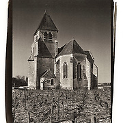 An old stone church is located amidst a vineyard in the countryside near the Chablis region of France.