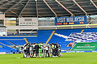 Football - 2020 / 2021 Sky Bet Championship - Cardiff City vs Swansea City - Cardiff City Stadium<br /> <br /> Swansea form a team huddle on the pitch after their South Wales derby victory scoreboard reading bluebirds 0 swansea 2 in background  in a stadium without fans because of the pandemic crisis<br /> <br /> COLORSPORT/WINSTON BYNORTH