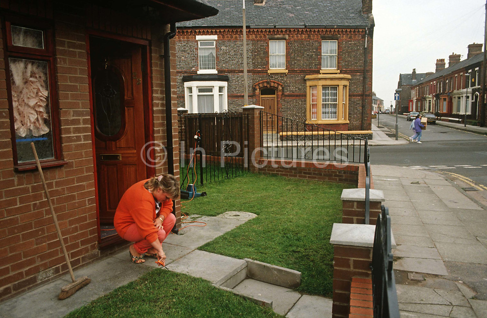 A house-proud housewife trims her lawn with a pair of scissors in new housing on a terraced Liverpool street. Stooping down to ground level, the lady snips and preens individual blades of grass on an almost perfectly manicured lawn. Her home is new, surrounded by the early 20th century and Victorian terraced housing that populates this part of north-western Britain. There are few cars and two other people cross the road without fear of approaching vehicles – the economy here is largely depressed. And yet, the female gardener has taken the trouble to mow her garden and then trim her esteemed plot. She wears an orange suit too, a splash of colour in an otherwise drab street.