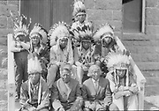 """336-MA36. """"Paiute Indians, Burns, Oregon"""" on the steps of Holy Family Catholic Church. Identifications: seated center left on lower step- Chief Captain Louey, old man seated center right on lower step- William Johnson. Indians with headdresses are from Pendleton."""