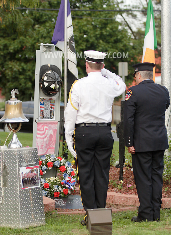 Town of Wallkill, NY - Two firefighters salute after placing a wreath at the base of a monument during a 9-11 memorial ceremony on Sept. 11, 2008.